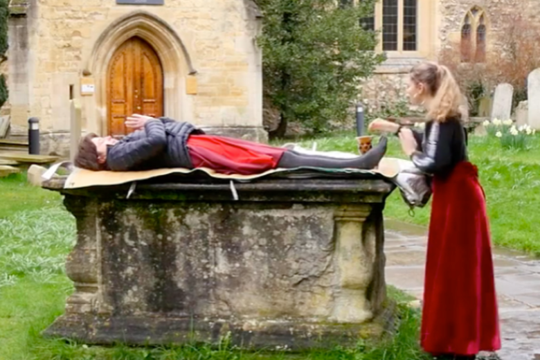 Man lies on ancient tomb. Woman in red skirt stands beside him.