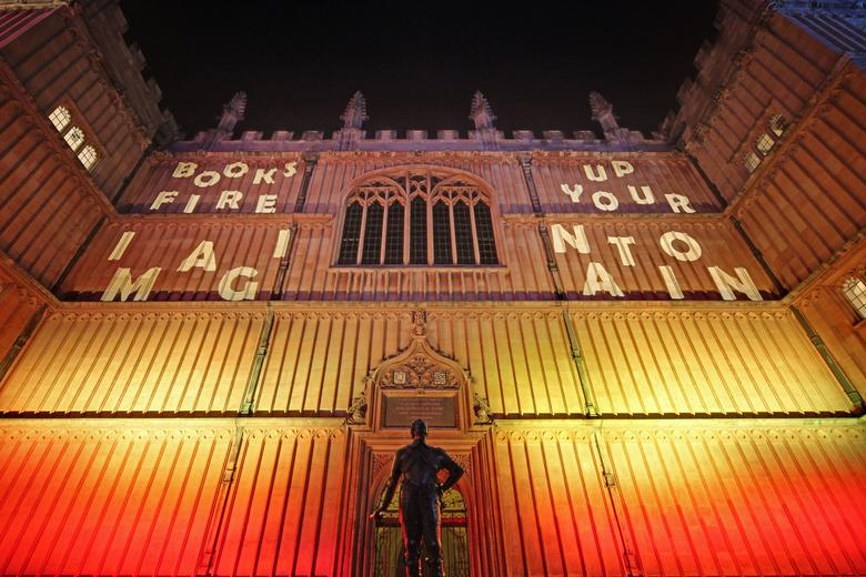 Photo of the side of the old bodleian library with fire colours projected onto it and the words 'Books fire up your imaginaiton'