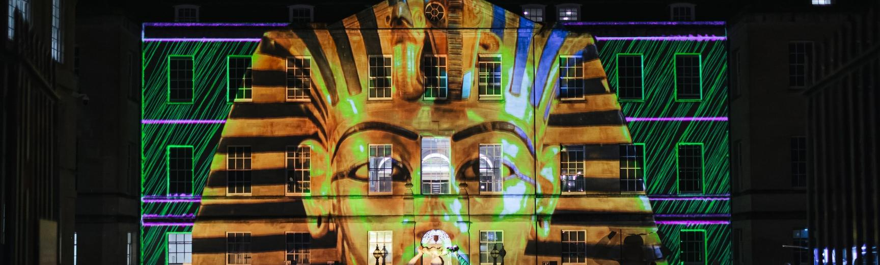 Front of TORCH building with the head of a golden Egyptian sarcophagus projected onto it