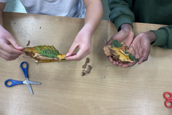 Hands of two children holding leaves over a table with scissors on.