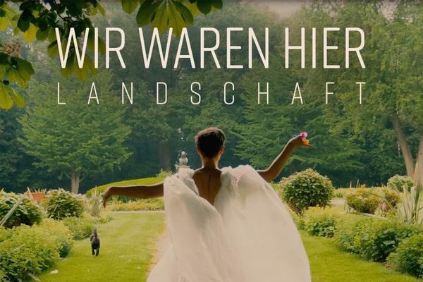 woman in floaty white dress walks down stone path in a green garden