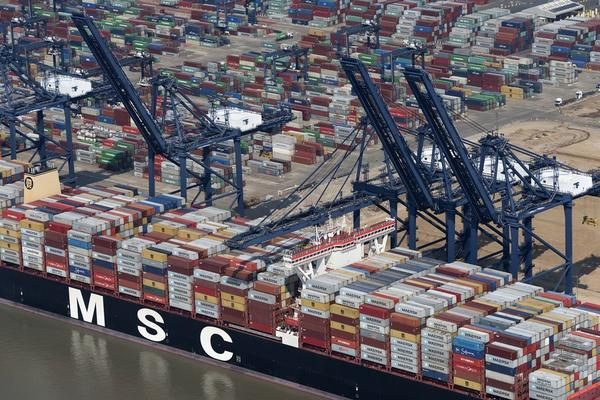 The boat MSC Tina moored at Felixstowe. The boat is loaded with containers and moored in front of four blue cranes.