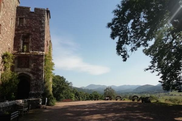 View of Muncaster Castle on a sunny day, with pink granite walls covered in climbing plants in the foreground and looking down mountainous Eskdale in the background.