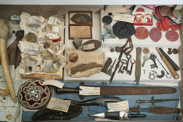 An overhead view of a tightly packed assemblage of approximately fifty objects. Most appear made of stone, metal, wax, or animal parts. Items include keys, weapons, wax seals, and a leather shoe.