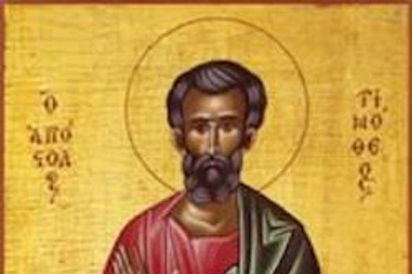 byzantine image of St Timothy with gold background, left hand rasied , right hand holding scroll, wearing red clothes with green robe