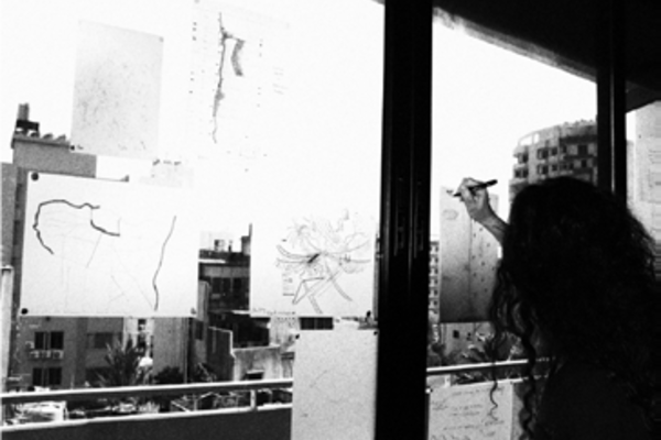 Image of a workshop participant drawing scores of the city through a window onto transparent paper during a workshop in Beirut.