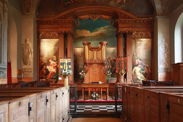 Image depicting nave of St Lawrence, Whitchurch Lane, Little Stanmore - East end with wooden pews, the altar in front of the organ flanked by a set of wooden columns (square and round). The walls depict religuous cenes framed with ornamental wood carvings