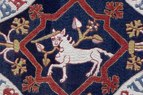 Blue tapastry of a white unicron with red , white, and gold border - medieval style