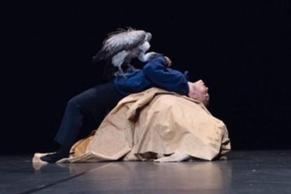 Theatre performer on stage bent backwards over a rock as a bird pecks his stomach in the manner of Prometheus