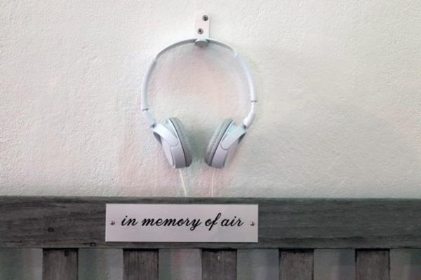 white headphones attached to wall above plaque which reads in memory of air