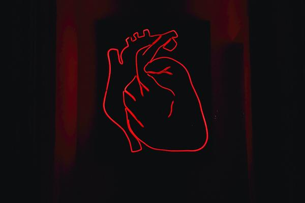 Image of a red neon heart outlined against a dark background. The background is mainly black with two dark red patches.