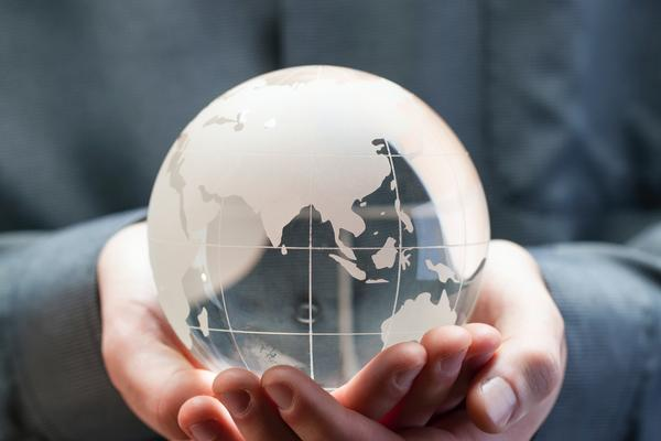 Person clutching glass globe, wearing grey shirt