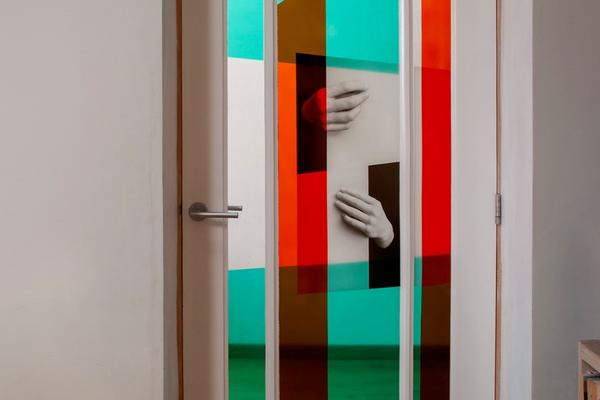 Door with three panels, showing 2 hands. Colour blocks of red and blue