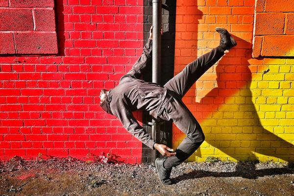 A dancer strikes a pose against a vivid red, orange and yellow wall