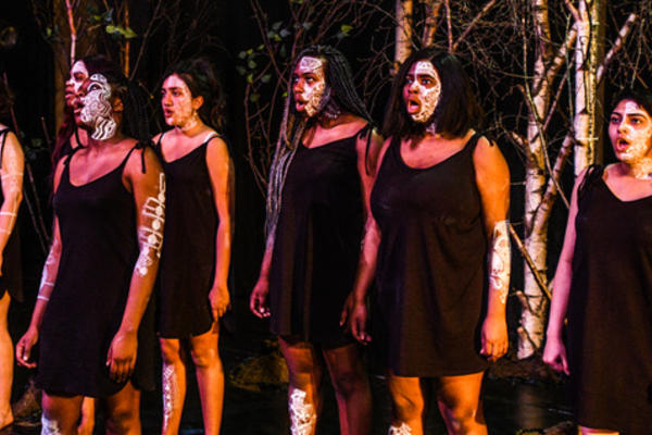 actors of colour from the chorus of medea line up next to each other. All wear black, with tribal markings on their face in white