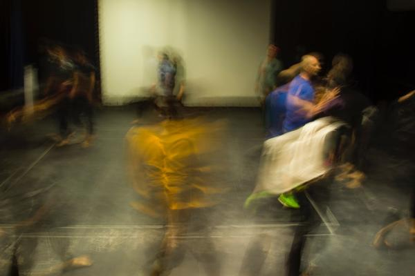 Actors rehearsing in a theatre, rays of light blur across the photo and make the people blurry