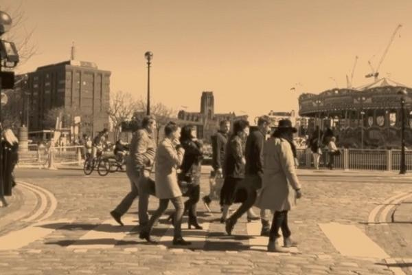 Image (sepia filter) displays about seven people on a pedestrian crossing in a city. Still image from short film 'Walk don't Walk by Samson Kambalu, 2016