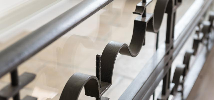 Photo of a metal bannister with a wavy pattern.