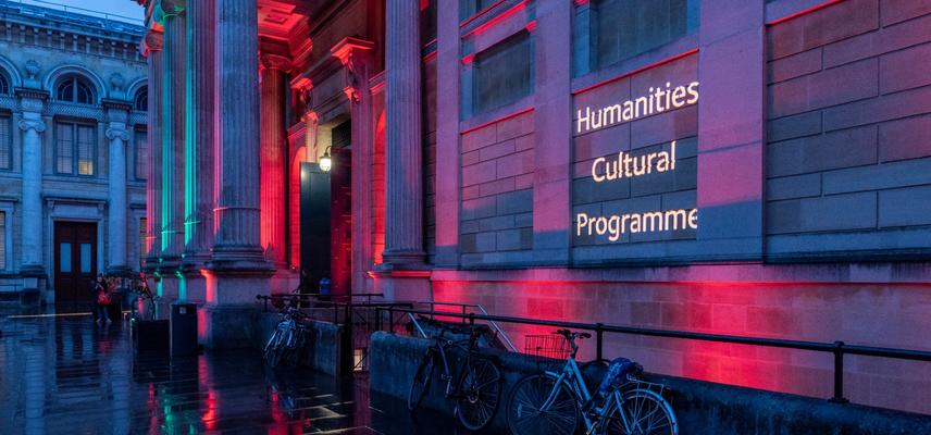 Museum front lit in blue and pink lights with 'Humanities Cultural Programme' projected in white letters