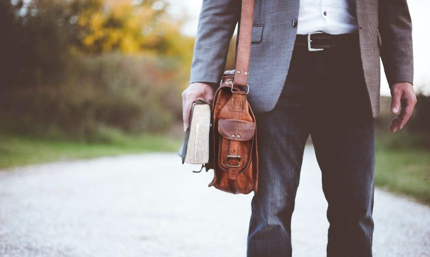 Person holding a satchel and book
