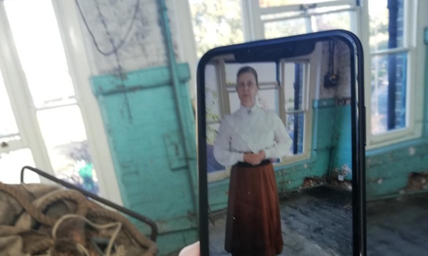 App showing a Victorian schoolteacher in a room