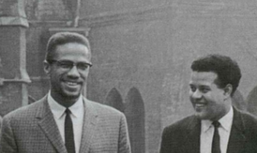 Black and white photograph of Malcom X and another man, smiling with Oxford buildings in background