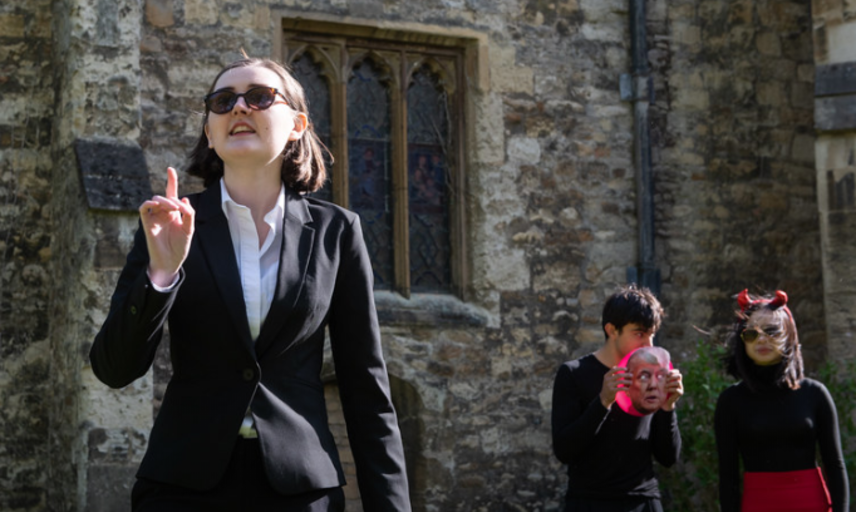 woman in black suit pointing up, man and woman behind her looking on all infront of St Edmunds Hall building