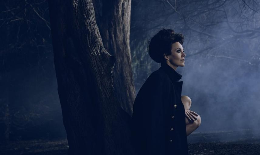 Image of Medea, woman in black cloak and fog in background