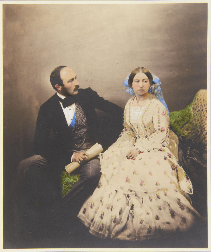 Hand-tinted photograph. Prince Albert is looking at Queen Victoria, who is looking away. The Queen is wearing a white dress and a veil.