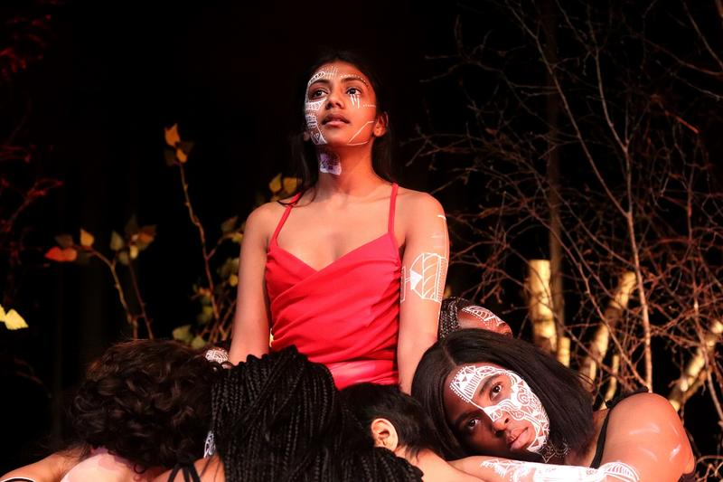 medea actress of colour in a red top, surrounded by the chorus wearing black clothes. All have tribal patterns on left hand of face in white