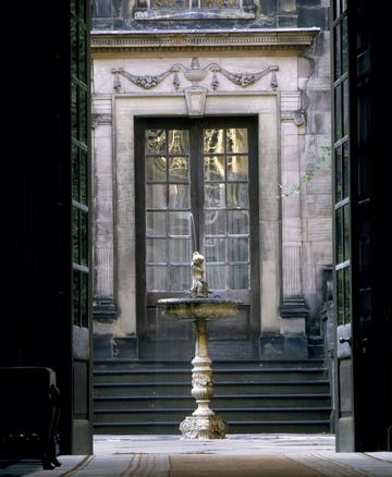 A photography taken from an interior space at Dunham Massey, looking towards a courtyard, where a fountain stands. Behind the fountain, there are the heavy glass doors of a different room that opens to the same courtyard but at a higher level (six steps).