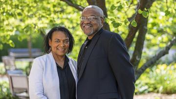 Photo of Lorna Dawes and Kwame Dawes stood smiling underneath a tree.