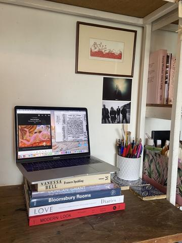 An open laptop balanced on a pile of books relating to the Bloomsbury Group. These items are placed on a desk with a jar of pens and pencils and decorative tiles, with art posters hanging on the wall above.