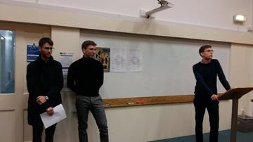 Three members of the OUBS committee giving a speech. One stands at a lectern; the other two stand by the door to the left of the photograph. The conference poster is visible in the background.