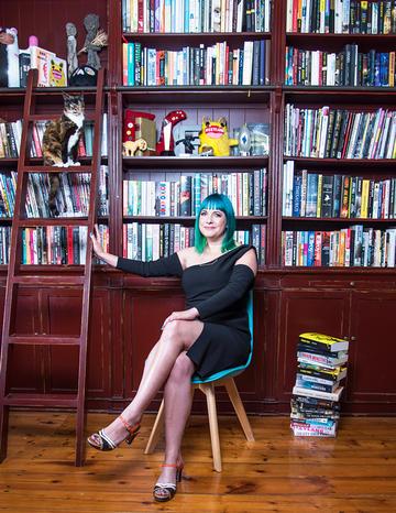 Lauren Beukes sitting on chair in front of wooden bookshelves
