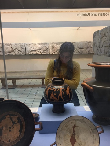 Abi examines a Greek vase in a museum setting. She has her arms crossed and is looking at it thoughtfully.