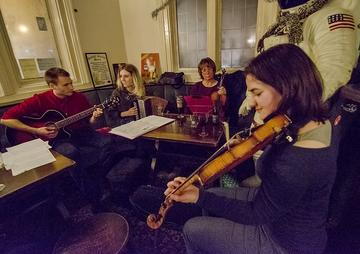 Image depicting four musicians in a pub playing English folk songs together of which two are playing the violine, one the guitar, and another the accordion.