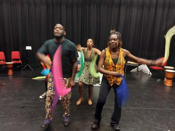 Four performers, waving colourful cloths which are blurred by motion