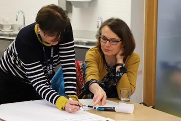 Two members of support stuff discussing and making notes on a project sheet.