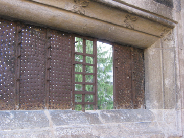 medieval window with metal inserts and stone surround