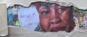 Graffiti art of Toni Morrison showing through ripped paper