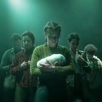 Production image - a young woman looks down at a baby in her arms, flanked by four weary travellers