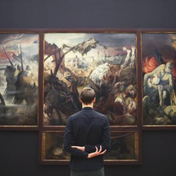 Person standing facing a large painting