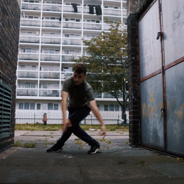 Dancer reaches for the ground in an urban alleyway
