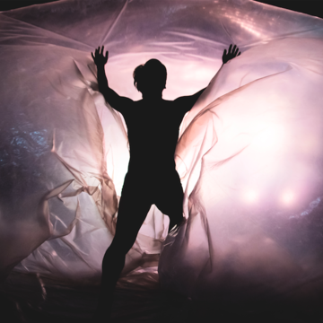 A dancer silhouetted against a large, purple, transparent, glowing egg shape, with arms outstretched.
