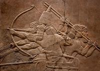 A stone carving showing 4 men holding spears