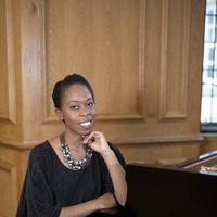 woman in black dress sits at a piano smiling at the camera