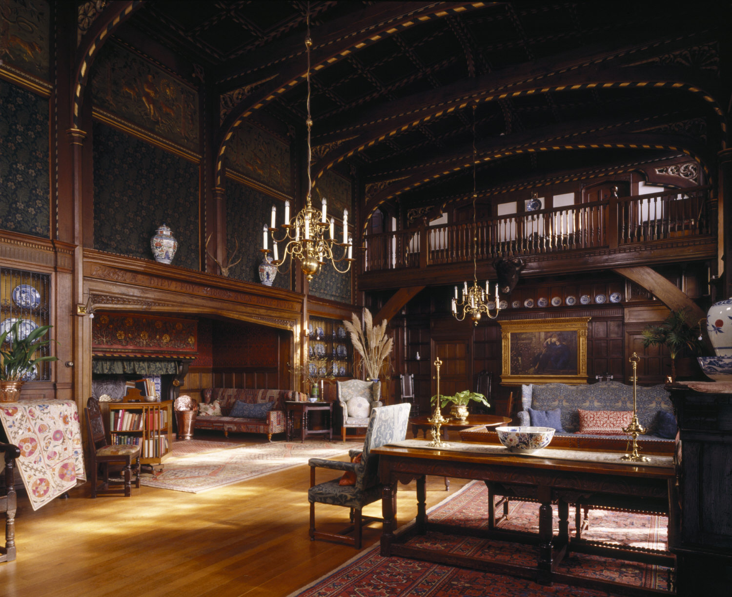 A photograph showing the large, wood-panelled interior of the Great Parlour at Wightwick Manor, Wolverhampton, filled with Arts and Crafts furniture and decorative objects. The wooden ceiling features decorative painting and two large brass chandeliers.