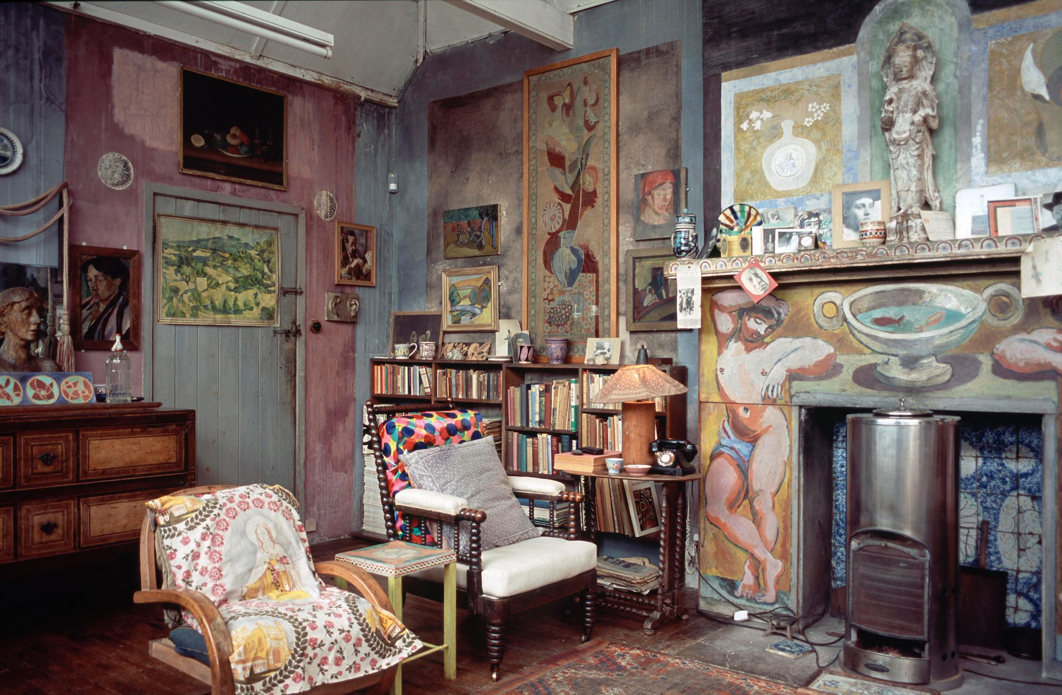 A cluttered corner of an indoor art studio - walls painted in various block colours, two chairs with multicoloured cushions, paintings and sculptures covering the walls. A bookshelf in the background and an unlit fireplace with a tiled and painted facade